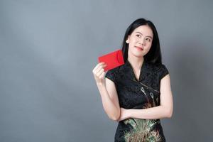 asiatische frau trägt chinesisches traditionelles kleid mit rotem umschlag foto