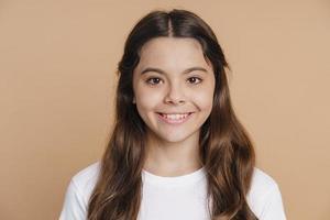 lächelndes, positives Teenager-Mädchen, das auf einem braunen Hintergrund posiert foto