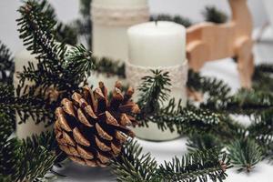 Drei Weihnachtskerzen, Kiefernzweig und Holzhirsch foto