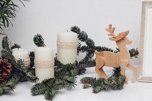 drei Weihnachtskerzen, Kugeln, Kiefernzweig und Holzhirsch foto