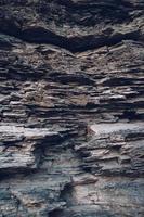 Oberfläche einer Steinmauer. schwarzer Steinhintergrund. Steinhaufen Hintergrund foto