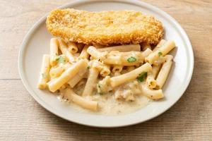 hausgemachte Quadrotto Penne Pasta weiße Sahnesauce mit gebratenem Fisch foto