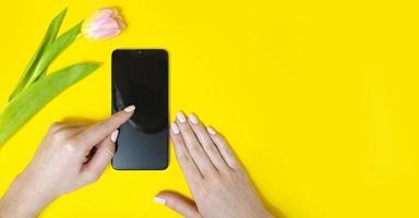 Das Mädchen hält das Telefon in der Hand. Durchblättern foto