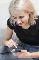 Mädchen genießt Musik in drahtlosen Kopfhörern. wählt Musik auf dem Telefon aus. foto
