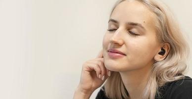 Mädchen genießt Musik in drahtlosen Kopfhörern. moderne Technologien. foto