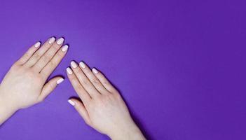 weibliche Maniküre auf hellem Hintergrund. lila foto