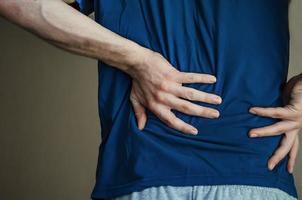 ein Mann, der ihm den Rücken zuhält. Rückenschmerzen. foto