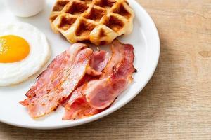Spiegelei mit Speck und Waffel zum Frühstück foto