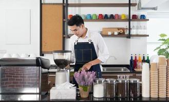 junger asiatischer Barista mit Kaffeemaschine, um Espresso im Café zu brauen foto