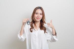 Porträt schöne asiatische Frau mit Autoschlüssel auf weißem Hintergrund foto