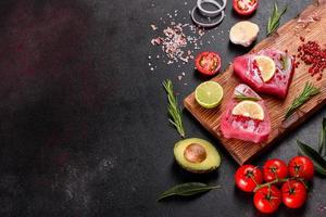 frische Thunfischfiletsteaks mit Gewürzen und Kräutern auf schwarzem Hintergrund foto