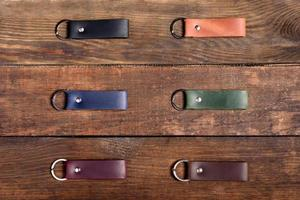 Set aus Leder Schlüsselanhänger mit Metallring auf Holzuntergrund foto