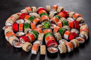 frische köstliche schöne Sushi-Rollen auf dunklem Hintergrund foto