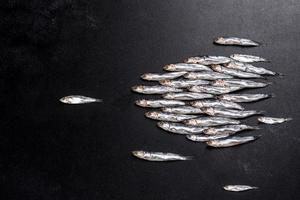 mehrere mit Fisch gesalzene Sardellen auf einem dunklen Betontisch foto