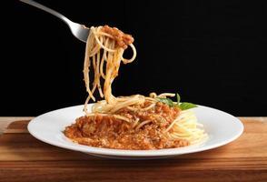 Hand hält eine Gabel mit Spaghetti und roter Soße in weißer Schale foto