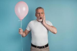 Überraschter älterer Mann, der einen rosa Ball in der Hand hält foto