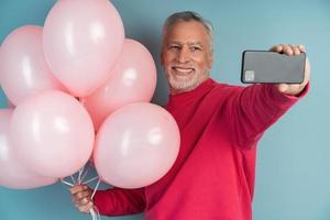 fröhlicher, lächelnder, grauhaariger Mann mit Eiern auf blauem Grund foto