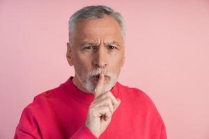 älterer Mann zeigt Geste, um ruhig zu sein foto