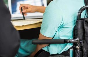 Junge behinderte Frau sitzt im Rollstuhl mit Kollegen im Büro foto