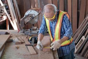 Senior asiatischer männlicher Tischler in der Holzfabrik. foto