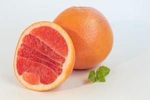 Grapefruit auf einem weißen Teller mit einem Zweig Minze. isolieren. foto