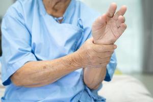 asiatische ältere Patientin spürt Schmerzen in ihrem Handgelenk und ihrer Hand foto