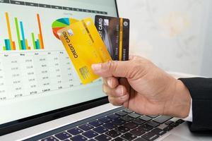 asiatischer Buchhalter, der online mit Kreditkarte arbeitet foto