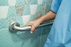 asiatische ältere Frau Patientengebrauch Griffsicherheit in der Toilette foto