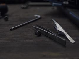 Pinzette und ein Inbusschlüssel liegen auf einem Holztisch. Werkzeuge auf dem Tisch foto