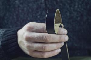 Handwerker hält ein echtes schwarzes Lederarmband in der Hand foto