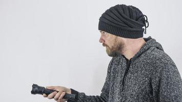 Ein bärtiger Mann hält eine Dioden-Taschenlampe in der Hand foto