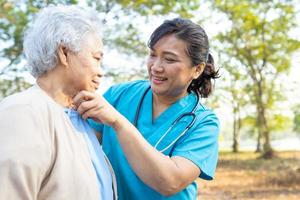 Arzt Hilfe und Pflege asiatische Seniorin zu Fuß im Park foto