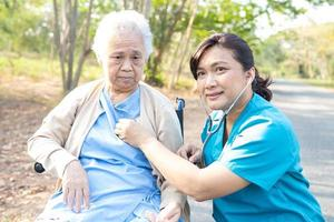 Arzt mit Stethoskop, um den Patienten im Park zu überprüfen foto