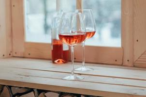 eine Flasche Roséwein und zwei gefüllte Gläser auf einem Fensterbrett foto