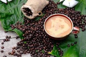 Tasse Kaffee mit Kaffeebohnen auf Holztisch foto