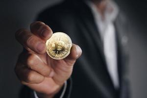 Geschäftsmann, der eine goldene Bitcoin auf dunklem Hintergrund hält, Kryptowährung foto