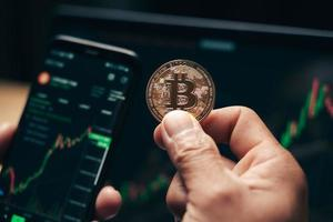 Geschäftsmann, der goldene Bitcoin auf dem Bildschirm des Computerhandelsdiagramms hält foto