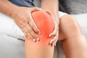 Frau sitzt auf dem Sofa und hat Knieschmerzen und massiert ihr Knie foto