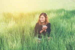 Frau sitzt auf grünem Gras, trinkt Kaffee und genießt die frische Luft foto