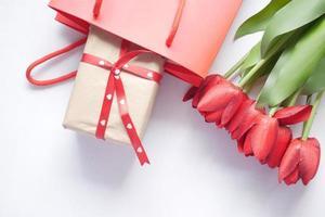 Geschenkbox in einer Einkaufstasche und rote Tulpenblume auf dem Tisch foto