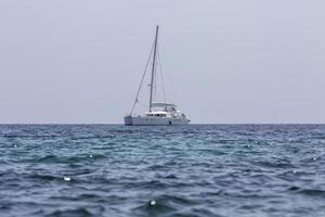 weißer Segelbootkatamaran am Meer in der Nähe von Strand. foto