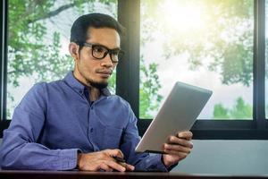 Mann trägt eine Brille, die E-Mails auf dem Tablet liest, zu Hause arbeiten foto