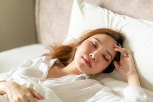 Porträt schöne asiatische Frau, die auf dem Bett mit weißem Kissen schläft foto