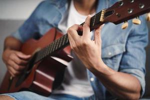 Genießen Sie den Mann, der auf dem Sofa im Wohnzimmer übt oder Gitarre spielt foto