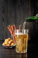 Bier gießt aus der Flasche ins Glas, schwarzer Holzhintergrund foto