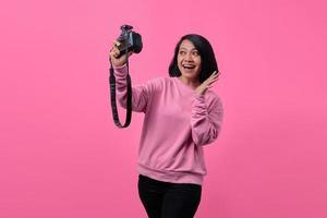 schönes Mädchen, das Selbstporträt mit professioneller Kamera macht. foto