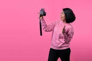 schönes Mädchen, das ein Selbstporträt mit professioneller Kamera macht. foto