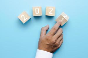Hand von Geschäftsleuten dreht 2021 bis 2022 auf Würfelbox foto