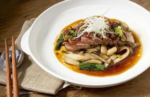 Thunfischsteak in einem weißen Teller wird auf einen Holztisch gelegt, japanisches Essen foto