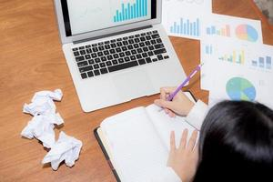Geschäftsfrau, die auf Notebook am Schreibtisch schreibt. foto